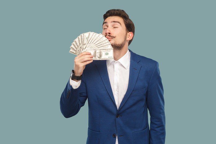 Man holding fan of money in hand and breathing in.