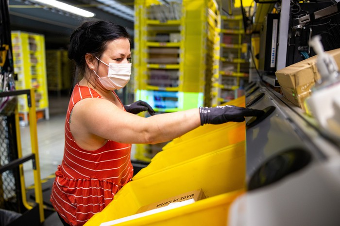 Amazon employee working in a fulfillment center while wearing a facemask.