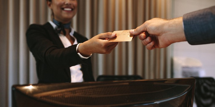 Man paying with a credit card at a hotel front desk