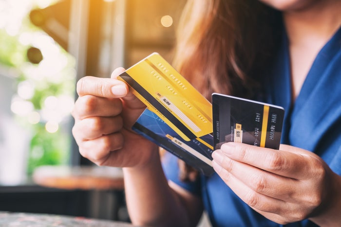 Person holding several credit cards.