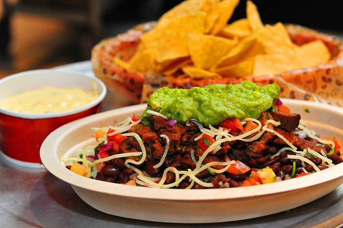 A Chipotle burrito bowl sits on a table with queso and chips sitting nearby