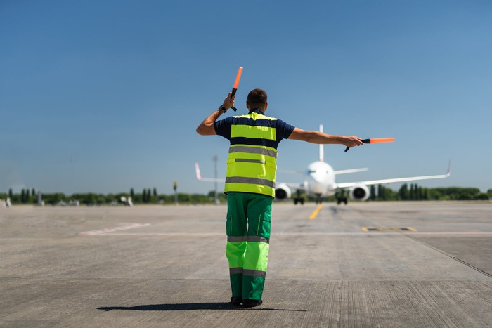 A ground worker guides an airplane to the gate.