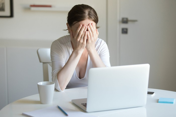 Woman sitting at laptop, covering her face