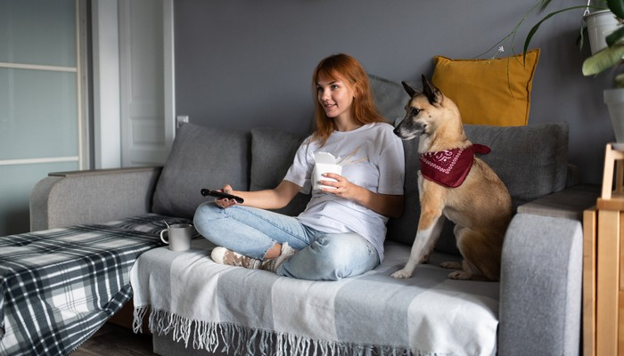 Woman sitting on couch next to a dog while holding a TV remote