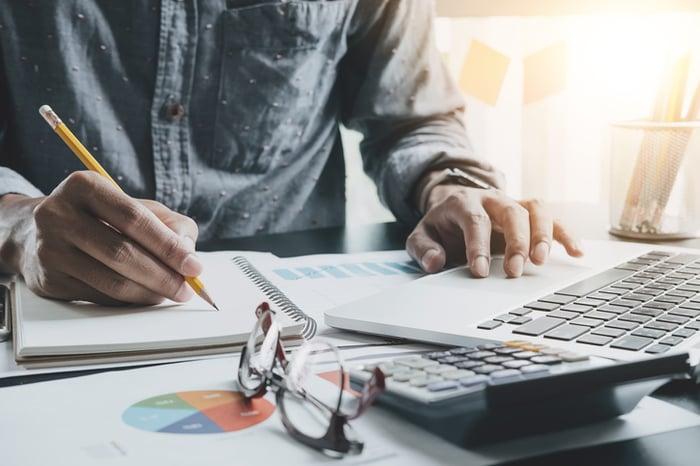 A man making calculations at his desk.