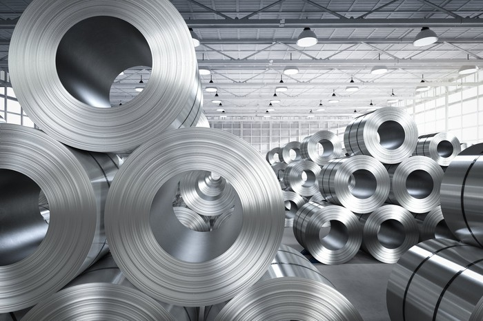 Rolled metal products piled in a large warehouse.