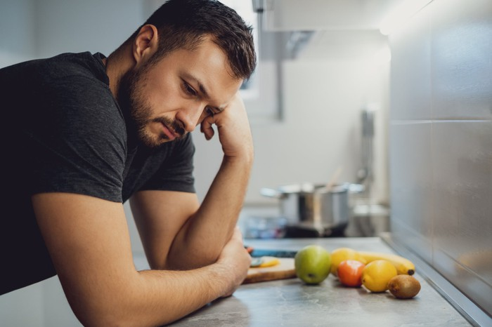 Man with somber expression leaning on kitchen counter