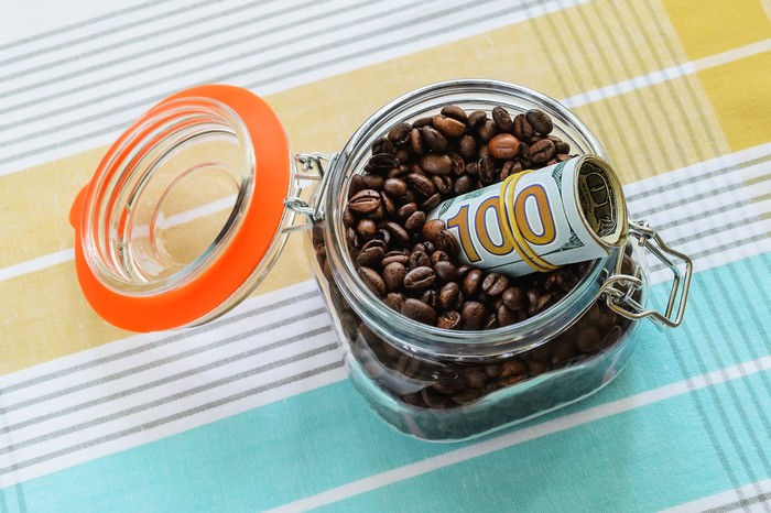 A roll of hundred-dollar bills sticking out of a glass jar full of coffee beans.