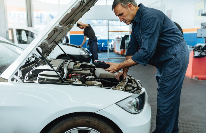 A man diagnosing a car for repair.