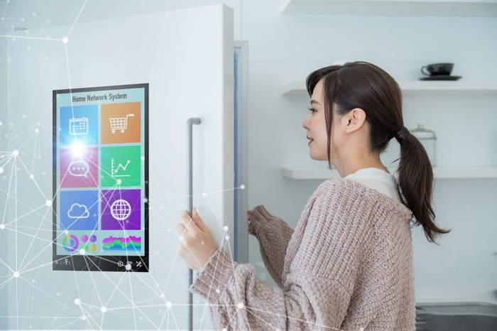 A woman opening a refrigerator with a digital screen on the door and illustration showing internet connectivity.