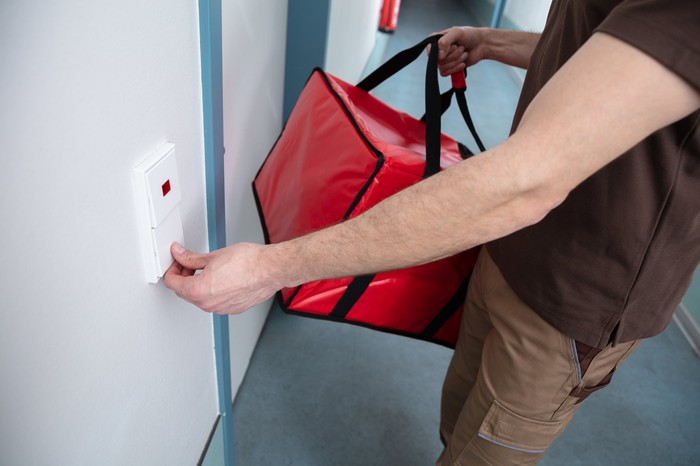A delivery man carrying a large red cooler bag rings a doorbell in an empty apartment building hallway.