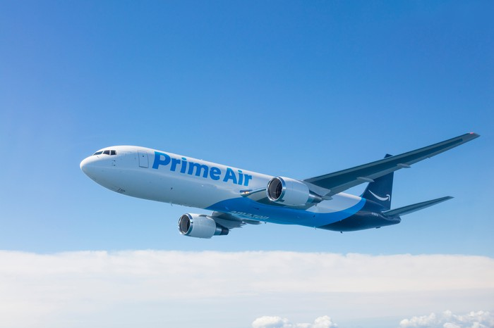 An Amazon Prime Air plane flying through the air in front of a blue sky.