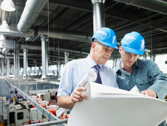 Two men wearing hard hats looking at blueprints over factory floor
