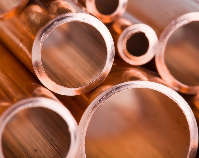 A stack of copper pipes in different sizes.