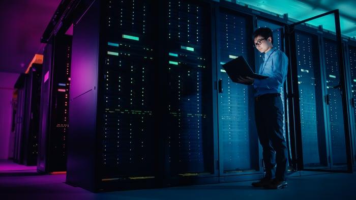 IT technician running maintenance program on laptop in front of servers