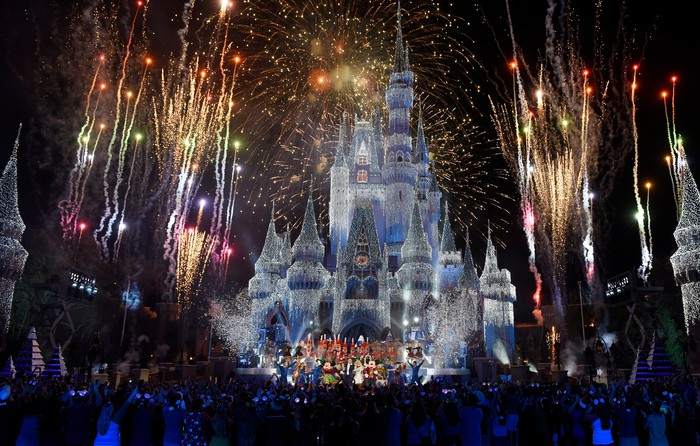 The Disney castle at night during a fireworks display.