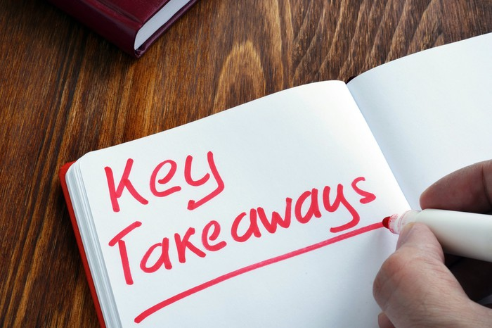 """Someone writing the words """"Key Takeaways"""" in red marker in a notebook."""