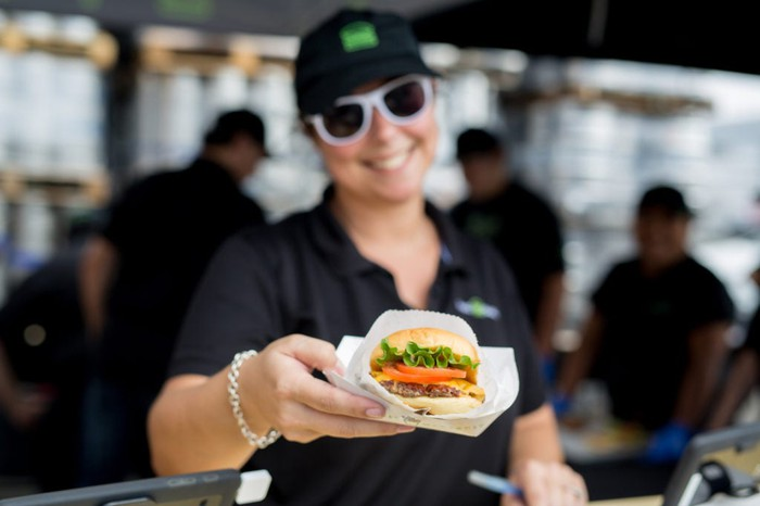 Shake Shack employee serving a burger