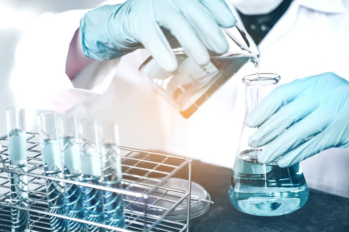 A person in a white lab coat working with chemicals.