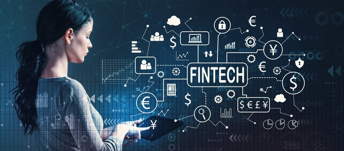 """A woman with a tablet punching in data. On the screen in front of her are various financial symbols and the word """"FINTECH"""""""