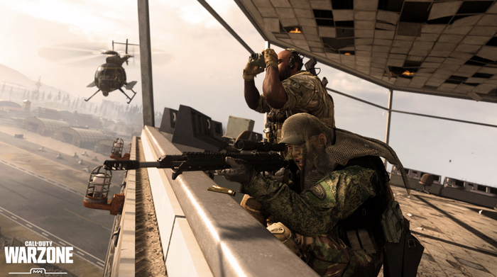 A screenshot from Call of Duty showing soldiers looking out from the roof of a building, with a helicopter flying in the background.