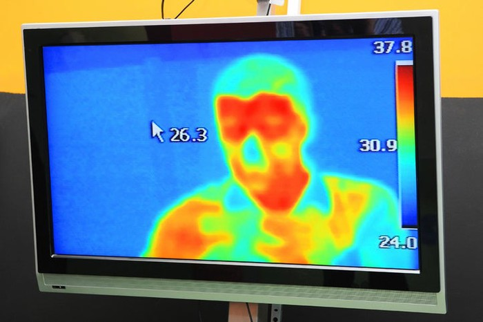 Screen showing infrared thermal image of a person from about the chest up.