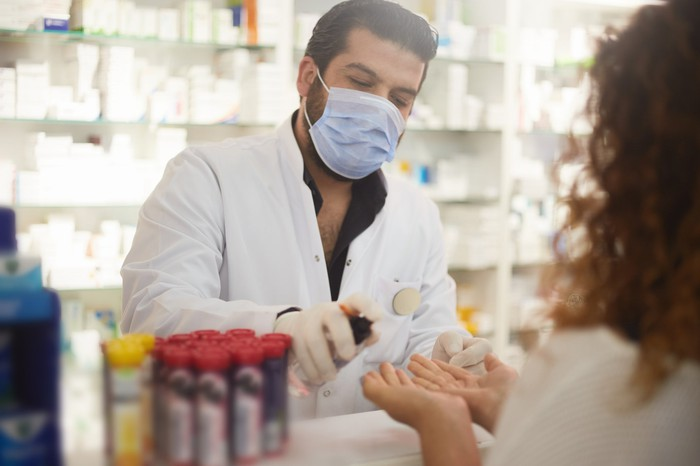 A pharmacist wears a face mask