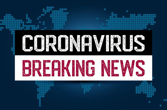 """Coronavirus breaking news"" in capital letters over top of a digital world map"