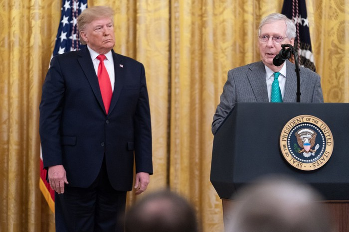 Senate Majority Leader Mitch McConnell speaking to reporters, while flanked by President Trump.