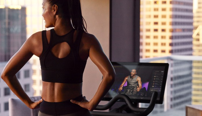 A Peloton user looks at skyscrapers out of her high-rise window during a stationary bike workout.