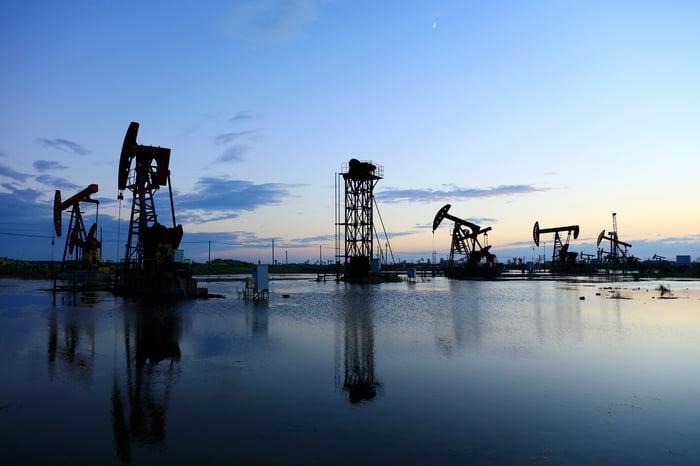 Pumpjacks at twilight in an oilfield.