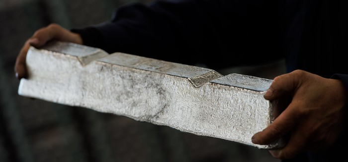 A person holding a raw aluminum ingot