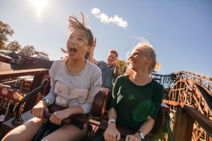 Two teenage girls enjoying a roller coaster ride.