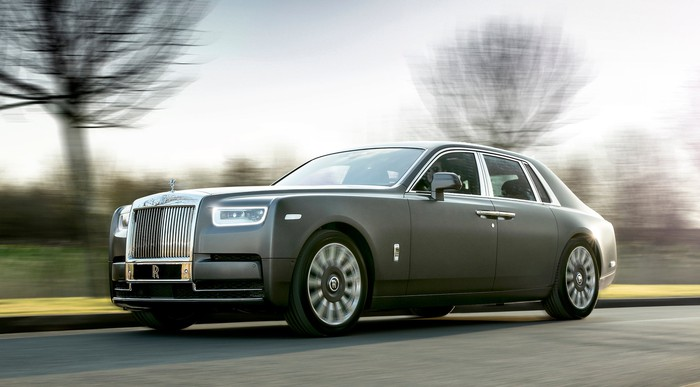A gray Rolls-Royce Phantom, a large ultra-luxury sedan, on a country road