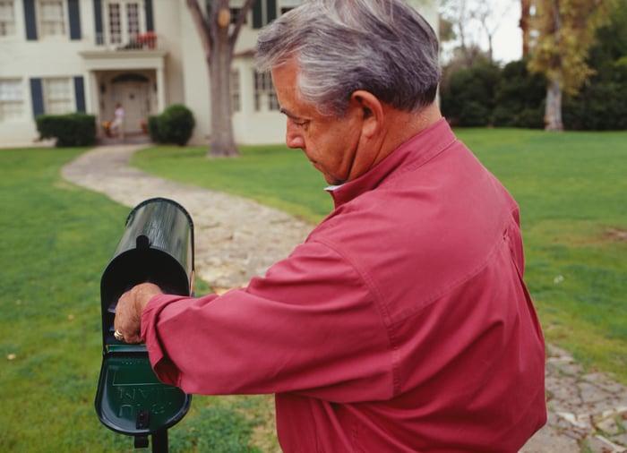 Older man reaching into mailbox