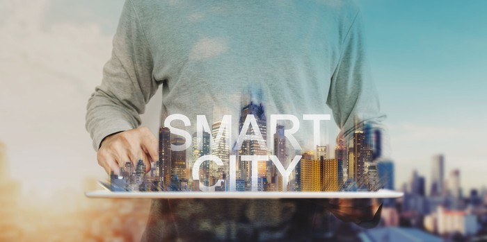 """Man holding model of city displaying the words """"Smart City."""""""