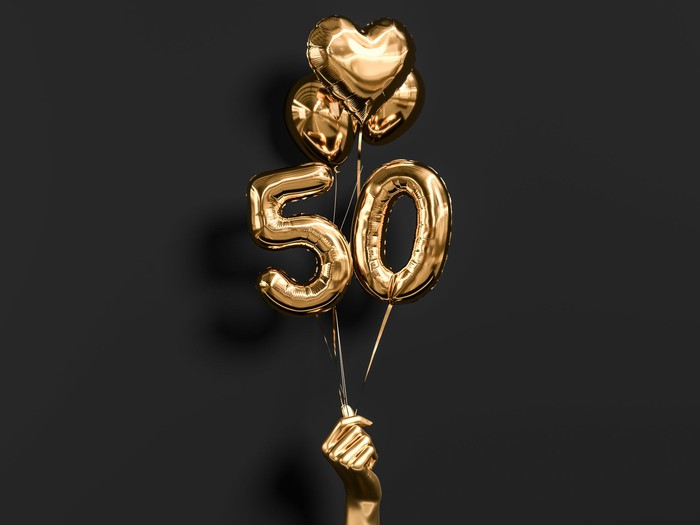 """A golden hand holds up numbered """"50"""" balloons with hearts."""