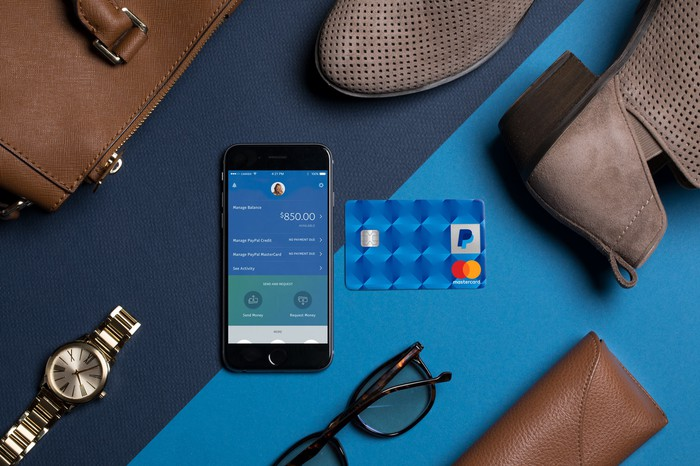 PayPal credit card and PayPal app on smartphone, on table with watch, glasses, shoes, and purse