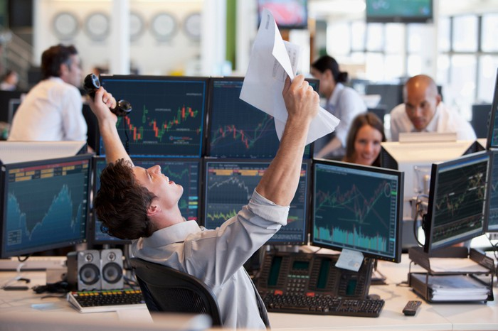 Man cheering in front of computer screens showing stock performance