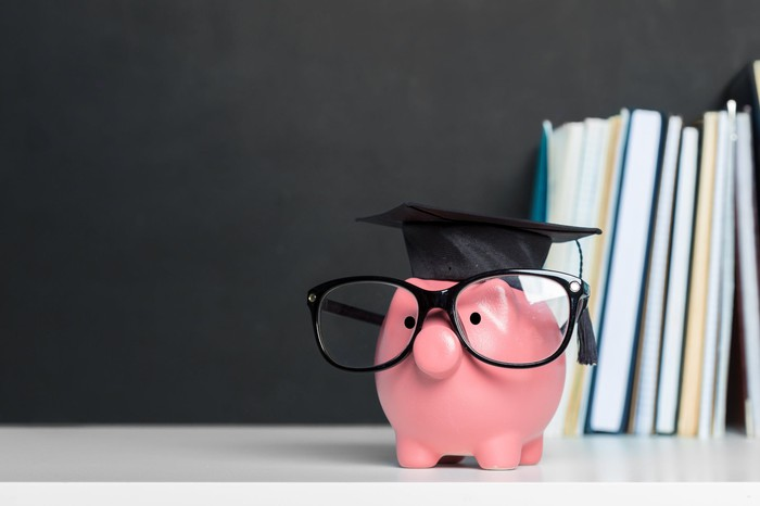 Piggy bank dressed with glasses and a mortarboard hat and books in the background.