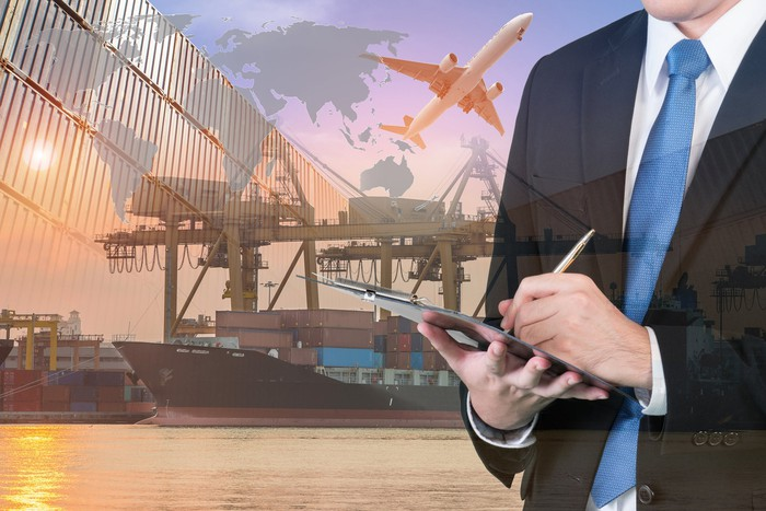 A man in a business suit writing a a clipboard with a container port in the background.