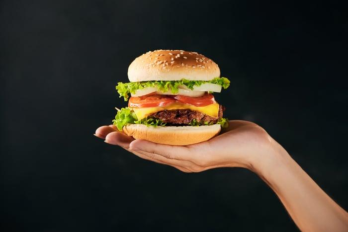 A hand holding up a hamburger.