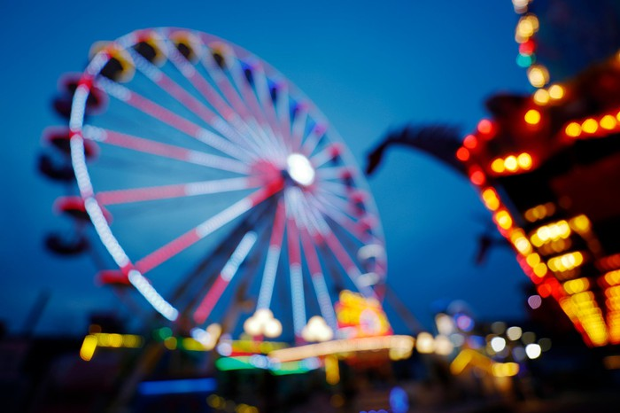 A blurry image of a ferris wheel and other carnival rides