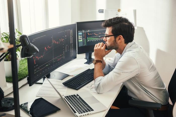 A trader looking at charts on computer screens.