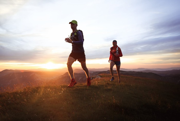 trail runners on a mountain at sunrise