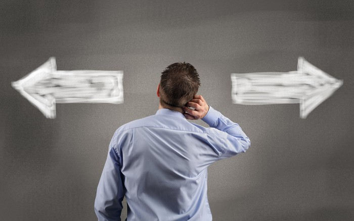 A businessman, facing away from the camera, scratches his head while looking at two arrows on the wall that point in opposite directions.