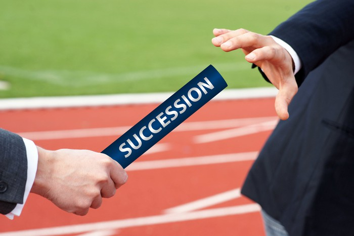 """A man in a suit on a track handing a baton marked """"succession"""" to another man in a suit."""
