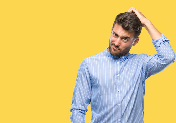 Man in collared shirt against yellow background scratching his head