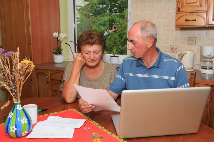 Older man and woman at a laptop looking at documents with serious expressions