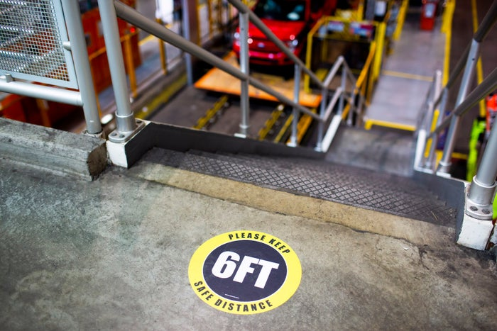 A reminder to stay 6 feet away from others is on the floor near a stairway at Ford's Dearborn Truck Plant in Dearborn, Michigan.